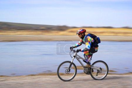 Speed motion mountain biker beside river