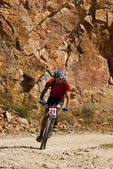 Mountain biker racing near rocks