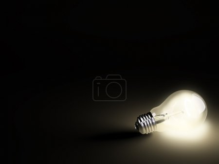 Luminous light bulb on black