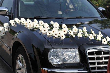 Photo pour Voiture sombre décorée de fleurs blanches - image libre de droit