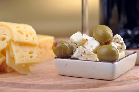 Sliced yellow cheese an olives
