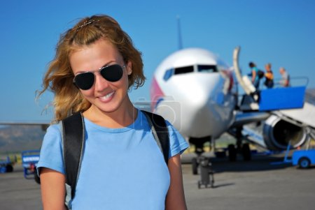 Photo for Young woman in front of the private airplane before departure - Royalty Free Image