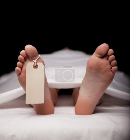 Deceased person covered in a sheet with a blank to...