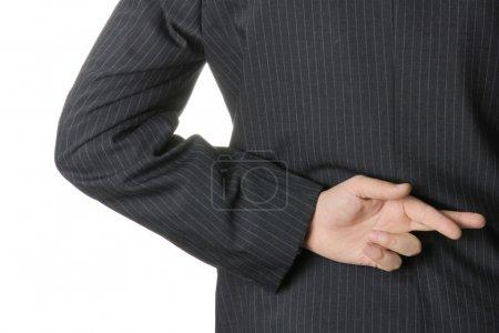Photo pour Homme d'affaires avec les doigts croisés dans le dos . - image libre de droit