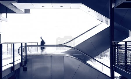 Photo for Business man move on escalator, blue tone - Royalty Free Image
